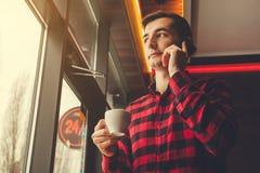 年轻人享用在咖啡馆的咖啡谈话在电话 早晨咖啡在一个工作日前 图库摄影