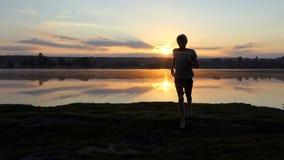 年轻人从湖跑到摄影师在日落在slo mo 影视素材