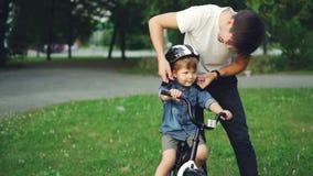 年轻人仔细的父亲的慢动作拿着自行车盔甲和谈话与他的关于然后投入盔甲的安全的儿子 股票视频