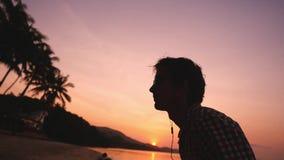 年轻人佩带的耳机和太阳镜由惊人的日落的海负责 他使沿沿海的奔跑慢 股票录像