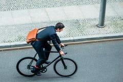年轻人佩带的西装,当骑一辆公共自行车时 免版税库存照片