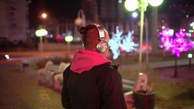 年轻人佩带的顶头电话画象,当走在街道上在城市在晚上和起动听时 股票录像