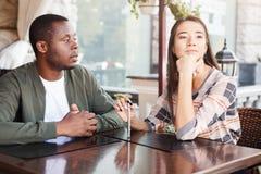 年轻人使女孩饮用的咖啡不耐烦在日期在咖啡馆 库存图片
