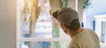 年轻人使用一块旧布和橡皮刮板,当清洗窗口时 免版税图库摄影
