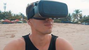 年轻人使用在海滩的虚拟现实玻璃 得到在使用的人VR耳机的经验在夏天旅行 影视素材