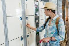 年轻人使用衣物柜的旅行妇女 免版税库存图片