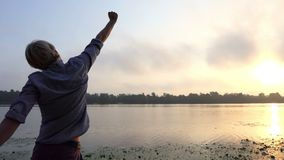 年轻人做在一个美丽如画的河岸的一呼吸的锻炼在日落 股票视频