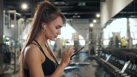 年轻人关闭有耳机的画象妇女听到音乐的在健身房的坚硬锻炼以后 有吸引力女孩微笑 股票视频