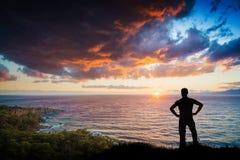 年轻人剪影反对日落的在海 库存图片