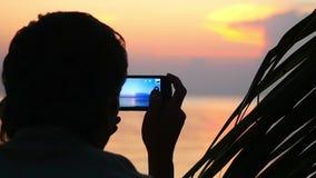 年轻人剪影拍与手机的照片在美好的日落背景  关闭 慢的行动 股票视频