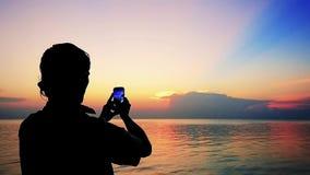 年轻人剪影拍与手机的照片在美好的日落背景  慢的行动 1920x1080 股票视频