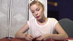 年轻人剪裁缝合与针并且用手穿线与方格的织品 影视素材