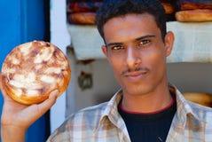 年轻人卖传统被烧的山羊乳干酪在市场上在萨纳,也门 免版税库存图片