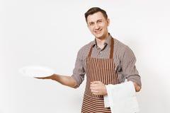 年轻人厨师或侍者镶边棕色围裙的,拿着白色圆的空的清楚的板材,毛巾餐巾的衬衣隔绝了  免版税库存照片