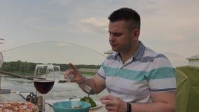 年轻人吃午餐用与菜的沙拉在开放大阳台的一家餐馆 r 股票录像