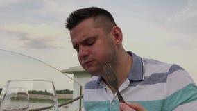 年轻人吃午餐用与菜的沙拉在开放大阳台的一家餐馆 r 影视素材