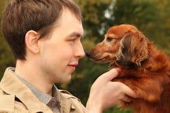 年轻人和他可爱的达克斯猎犬特写镜头 库存照片