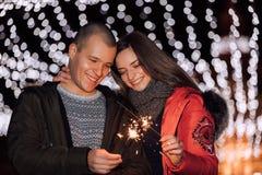 年轻人和他的女朋友获得与闪烁发光物的乐趣 库存照片
