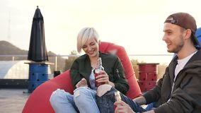 年轻人和女孩在大阳台咖啡馆饮用的能量饮料的多彩多姿的扶手椅子坐 获得两个的朋友乐趣 股票视频
