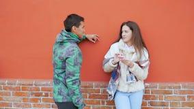 年轻人和女孩在房子的墙壁附近谈在街道上的身分 影视素材