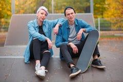 年轻人和女孩溜冰板者,户外在一明亮的秋天天 库存图片