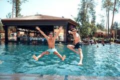 年轻人和女孩跳进水池 免版税库存图片