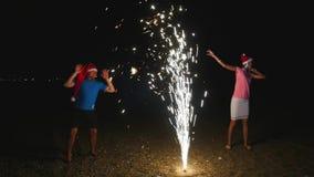 年轻人和妇女圣诞节帽子runnig烟花喷泉的发火花  股票录像
