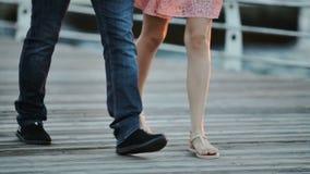 年轻人和妇女沿一个木码头走 恋人 反对太阳的黎明 股票视频