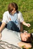 年轻人和妇女获得乐趣在夏天野餐 库存图片