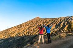 年轻人和妇女远足者传播的手,享用和满意对山顶视图 免版税库存照片