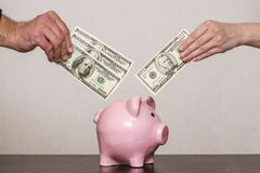 年轻人和年轻女人的手在家庭预算的存钱罐中投资金钱 夫妇存与存钱罐的金钱 图库摄影