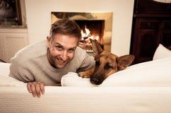 年轻人和狗拥抱在舒适家的德国牧羊犬逗人喜爱的画象在冬天 免版税库存照片