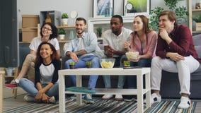 年轻人和笑妇女的看着电视一起吃在公寓的玉米花 影视素材