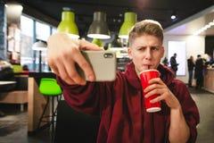 年轻人喝从一块红色玻璃的一个饮料并且做selfie 免版税库存照片