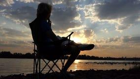 年轻人喝在一把折叠椅的咖啡与他的笔记薄在日落 股票视频