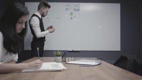 年轻人图画在显示信息的办公室板的圆形统计图表对介入工作女性同事 ?????????????? 股票录像