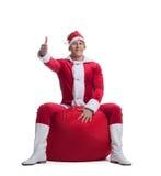 年轻人圣诞老人坐与存在的红色袋子 库存照片