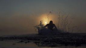 年轻人在一个朦胧的湖跑在日落在slo mo 影视素材