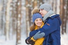 年轻人在一个森林里拥抱女孩在冬天 免版税库存图片