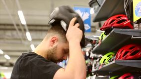 年轻人在一个立场附近站立在自行车商店 选择在一个小店的一件自行车盔甲 影视素材