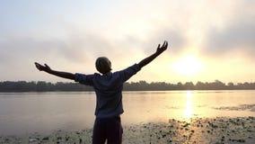 年轻人在一个美丽如画的河岸采取手在旁边在日落 股票视频