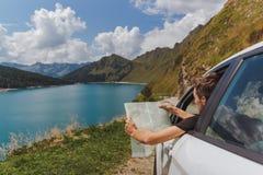 年轻人在与他的看地图的汽车的山丢失了发现正确的路 图库摄影