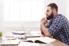 年轻人在从边的现代白色办公室注重了有膝上型计算机的人 免版税库存照片