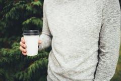 年轻人在他的手上拿着一杯咖啡 库存照片