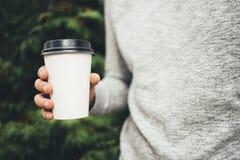 年轻人在他的手上拿着一杯咖啡 免版税库存照片