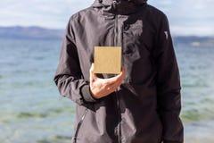 年轻人在他的手上的拿着一个礼物盒 免版税库存照片