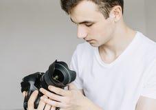 年轻人在他的手和神色上拿着一台照片照相机在尘土,一个肮脏的透镜的透镜 被隔绝的灰色背景 免版税库存照片