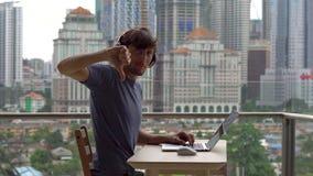 年轻人在他的膝上型计算机的自由职业者workes在一个阳台有充分市中心的背景的摩天大楼 远程 股票录像