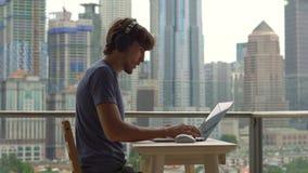 年轻人在他的膝上型计算机的自由职业者workes在一个阳台有充分市中心的背景的摩天大楼 自由职业者 影视素材