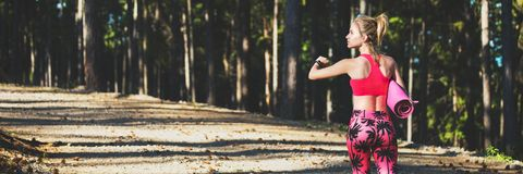 年轻人在佩带巧妙的手表和拿着瑜伽席子的森林里适合了运动妇女,轻易地胜过照相机 免版税库存照片